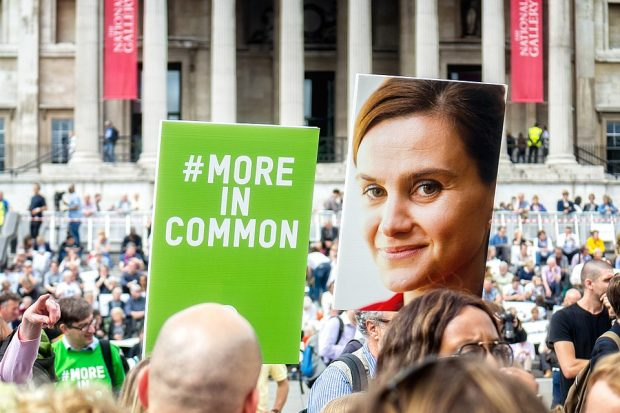 a crowd of people and a two large placards, one with an image of jo cox and one with the slogan #MoreInCommon