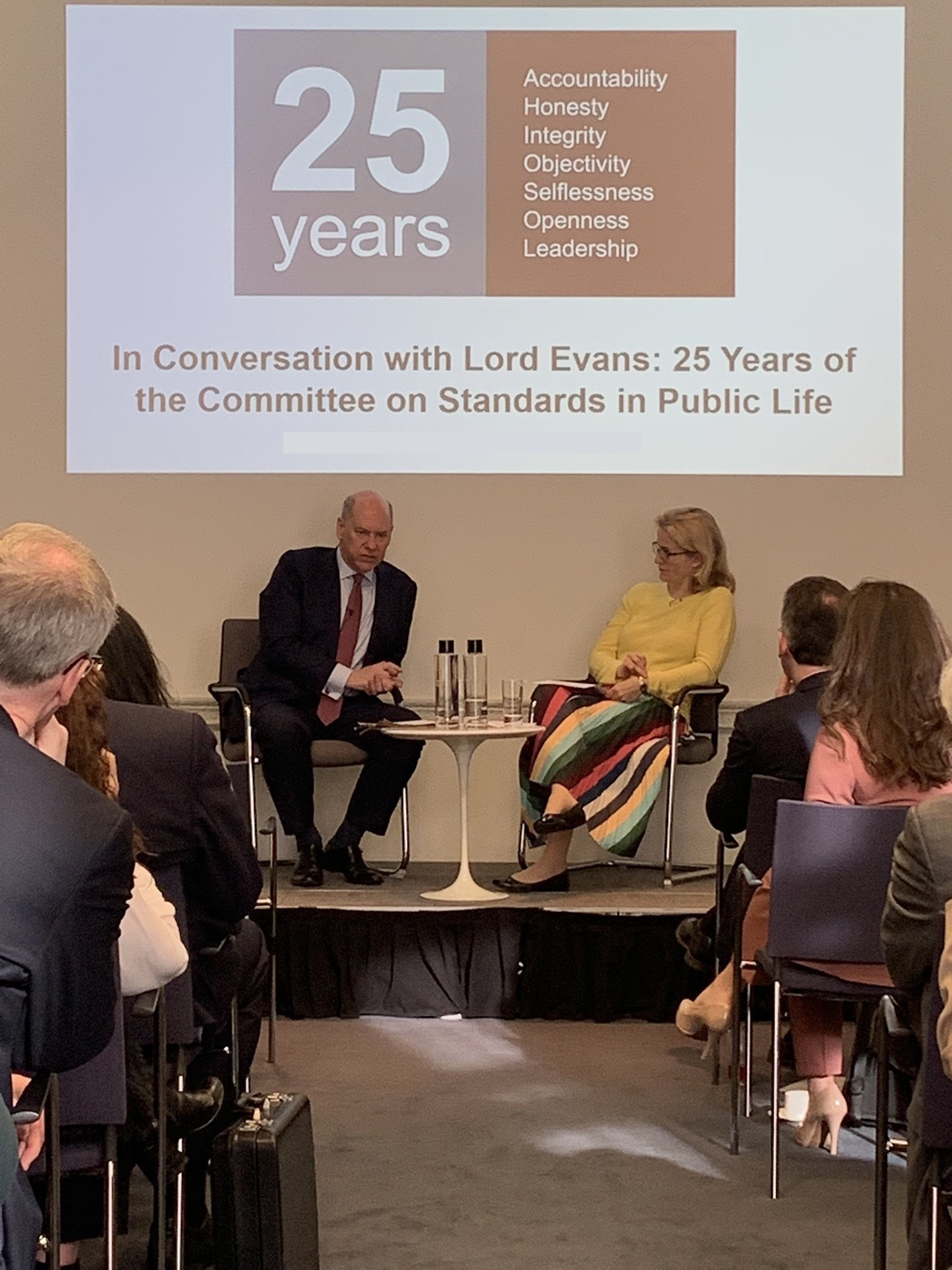 Lord Evans speaking to Hannah White in front of an audience at the IfG underneath a CSPL 25 years logo projected on the wall